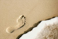 Footprint in sand next to wave