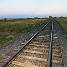 Low angle diminishing view of railroad tracks in rural setting at dusk