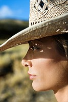 Close_up profile of mid_adult Caucasian woman wearing straw cowboy hat