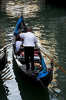Gondolier in Gondola with passengers on quiet canal _ reflections in water