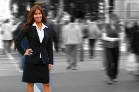Reddish brown hair model in business attire stands in front of gray moving crowd