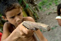 Child with toy gun in one of the Amazone communities, Cametá. Brazil