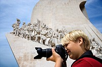 Caucasian boy looking through camera at the Monument to the Discoveries in Lisbon, Portugal