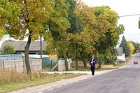 Woman walking along the road, Rawa Mazowiecka, Central Poland