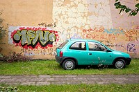 Graffiti on wall of building next to a turquoise car