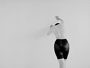 Woman with girdle leaning on a wall, Rear View, Black and White