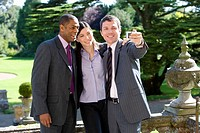 Young businessman with colleagues taking photograph of themselves outdoors, smiling