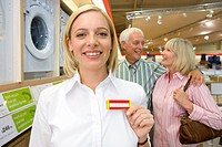 Shop assistant with hand to name badge by mature couple, smiling, portrait (thumbnail)
