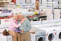 Mature couple shopping for appliances, woman embracing man, smiling, portrait