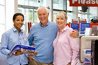 Mature couple shopping for computer, arm in arm by saleswoman, smiling, portrait
