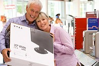 Mature couple shopping, man with computer in box, smiling, portrait