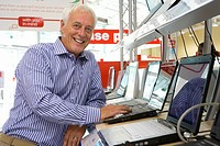 Mature man shopping for laptop computer, smiling, portrait