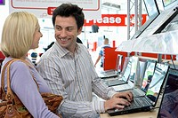 Young couple shopping for laptop computer, smiling at each other
