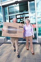 Mature couple leaving shop with television in box, smiling at each other