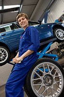 Female mechanic with wrench on tyre by elevated car, portrait, low angle view