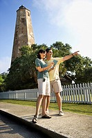 Mid_adult Caucasian couple sightseeing with lighthouse in background at Bald Head Island, North Carolina.