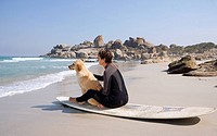Female surfer with dog on surfboard on beach, side view