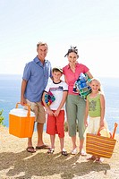 Family of four with cooler, towels and bag on beach, smiling, portrait