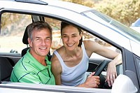 Couple in car, smiling, portrait