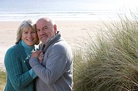 Senior couple embracing on beach, smiling, portrait