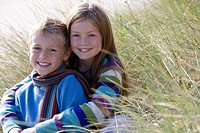 Brother and sister 6-8 years embracing on grass, smiling, portrait