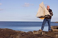 Senior man holding up model sailboat by sea, smiling, portrait