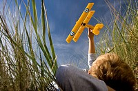 Boy 7-9 years holding up toy airplane whilst lying on long grass, low angle view