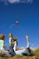 Family of four flying kite whilst sitting on grass, rear view