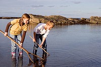 Boy and girl 7-9 years holding fishing nets in lake