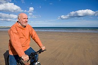 Senior man with bicycle on beach