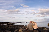Senior couple on rocks looking out to sea, man with arm around woman, rear view