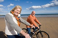 Senior couple cycling on beach, smiling, portrait, side view