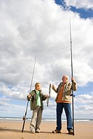 Grandfather and grandson 7-9 on beach with fishing rods and fish, smiling at each other, low angle view