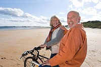Senior couple with bicycles on beach, smiling, portrait
