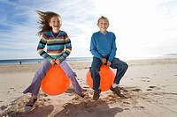 Girl and boy 8-12 playing on inflatable hoppers on beach, smiling, portrait