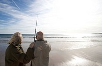 Senior couple on beach looking out to sea, man with fishing rod, rear view lens flare