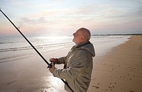 Senior man fishing on beach, dusk, side view lens flare
