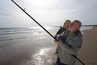 Senior couple on beach, man fishing, side view