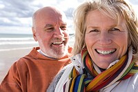 Senior couple on beach, smiling, portrait, close-up