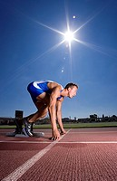 Male sprinter on starting block, side view sun flare