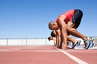 Male sprinters on starting blocks, low angle view