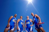 Group of male athletes, low angle view, lens flare