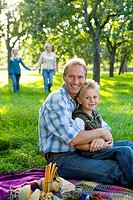 Family of four having picnic, father embracing son 7-9 smiling, portrait