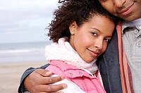 Young couple embracing on beach, portrait of woman