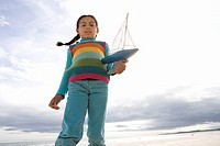 Girl 5-7 with toy boat on beach, portrait, low angle view