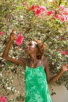 Mid_adult Black female smelling bougainvillea flower.