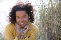 Young woman on sand dune, smiling, portrait