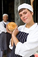 Female baker with pie by colleague, smiling, portrait