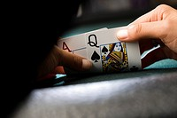 Woman looking at playing cards at poker table, close-up of hands