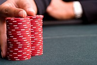 Woman with hand on pile of gambling chips, close-up